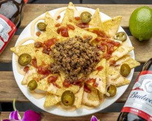 ミートナチョス Meat Nachos 当店人気のタコミートに特製サルサソースとチーズソースをたっぷりとかけたボリュームのあるアメリカのスタンダードスタイル。1度食べたらやみつきになる美味しさ!オーガニックトルティーヤチップス使用です。 These filling, classic American-style nachos are made with a generous amount of our popular taco meat, special salsa, cheese sauce, and organic tortilla chips. Once you try them, you will be hooked!